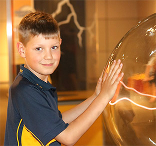 Lutheran Education home page insider insights image. Young boy with hands on a glass electromagnetic ball