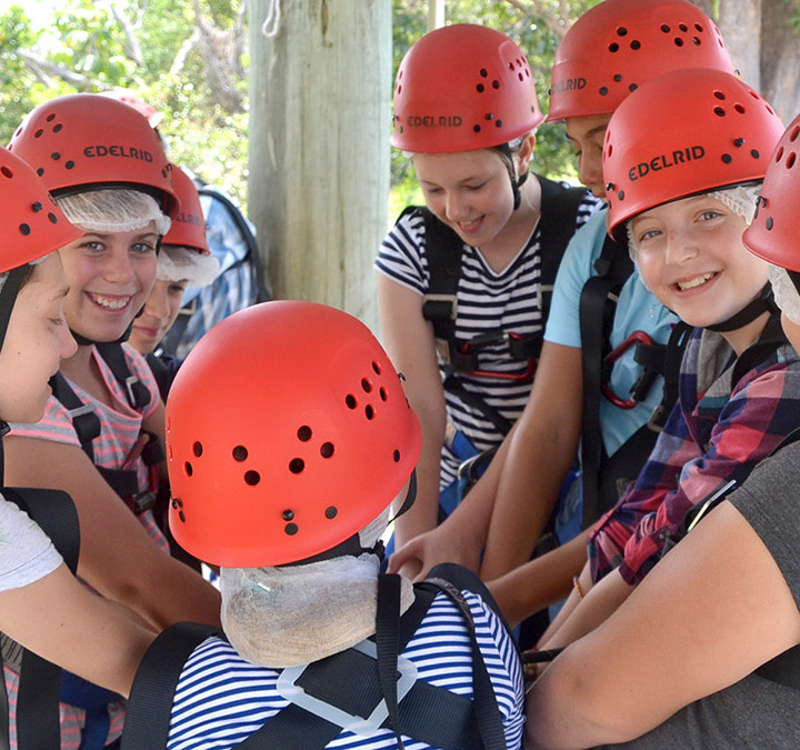 Outdoor education Female students in harnesses getting ready to climb