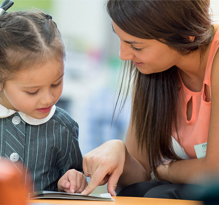 Parenting and schools – a learning partnership_Female teacher helping a very young student