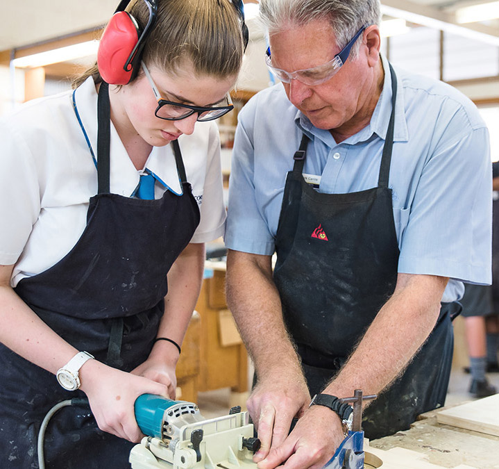 Vocational Education and Training Male teacher teaching female student woodcraft